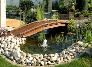 Exteriérové doplnky na mieru - drevený mostík nad jazierkom v záhrade.
